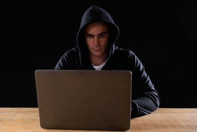 Man In Hood Using Computer